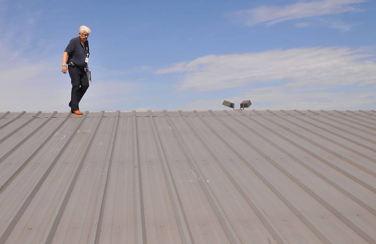 Roofer does hail damage inspection on metal roof