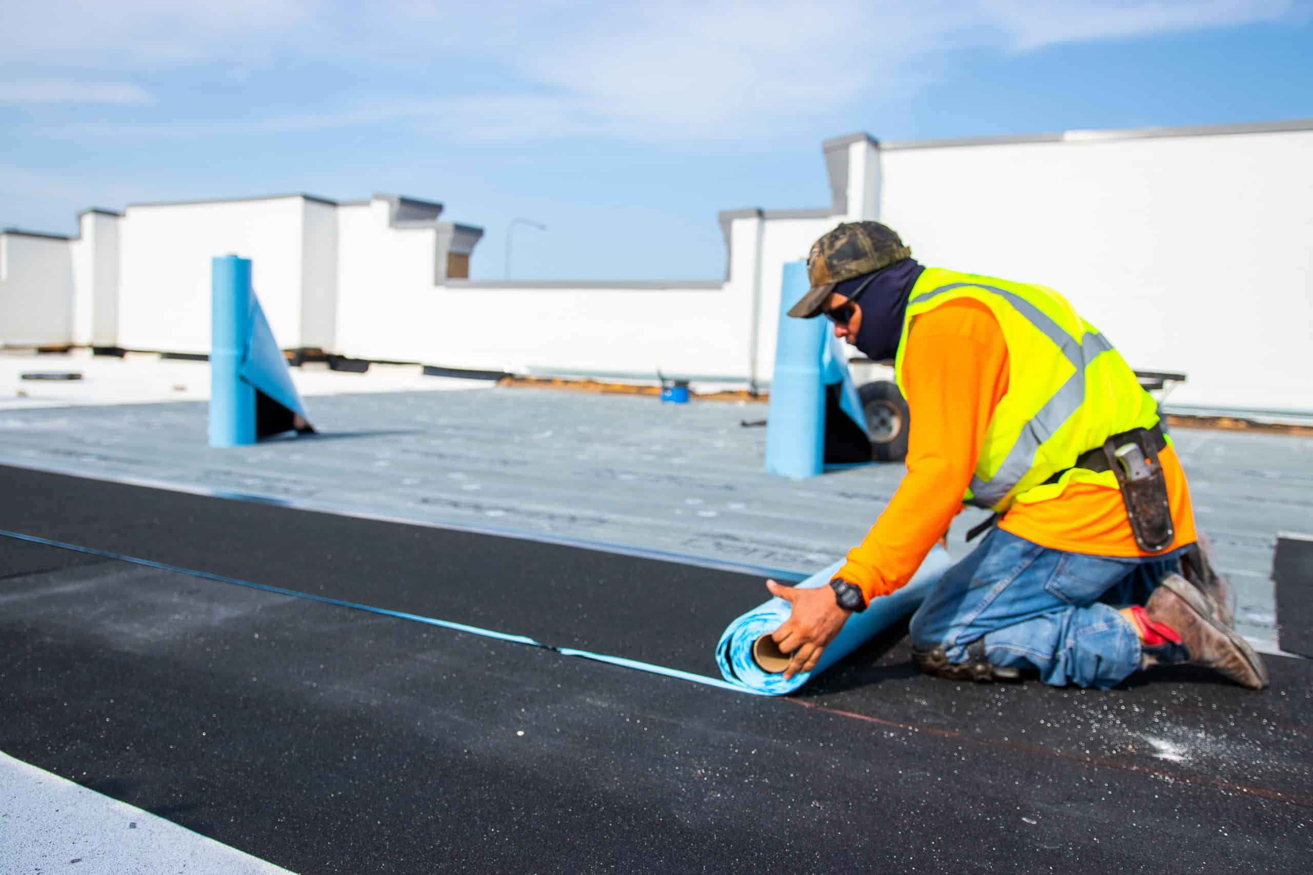 Certainteed Flintlastic SA roofing being unrolled and installed