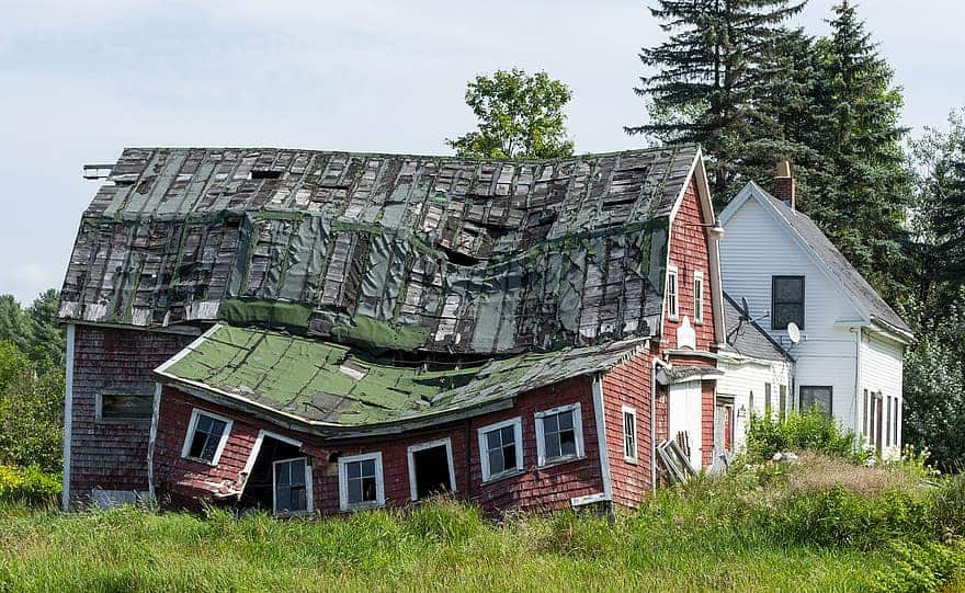 A barn with a badly damaged roof
